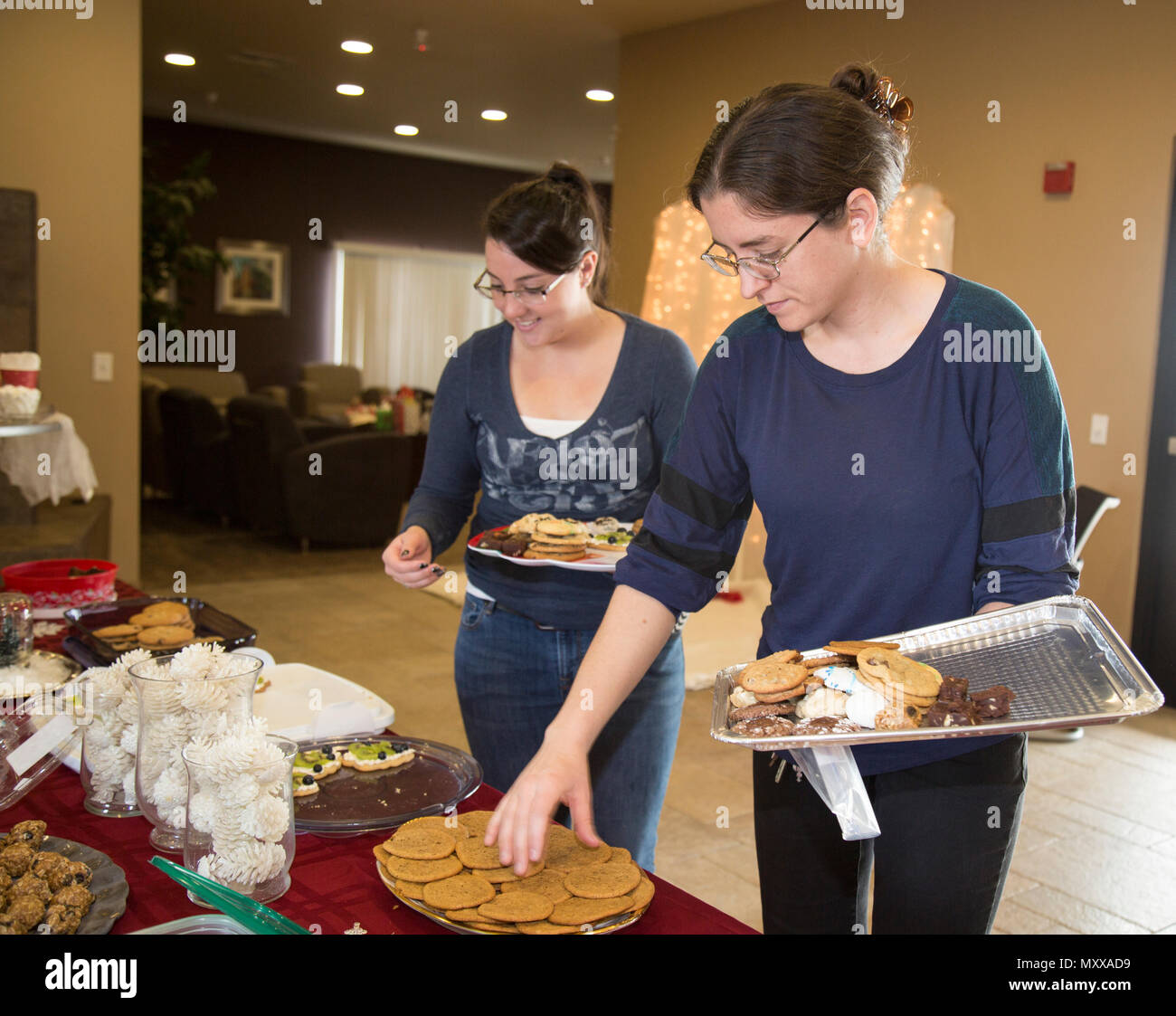 Military spouses, Jamie Teale and Erica King, enjoy a morning of exchanging cookies and ornaments aboard Marine Corps Logistics Base Barstow, Calif., Dec. 13. All of the attendees bring cookies and an ornament, then fill a tray each with a variety of goodies to take home. - Stock Image