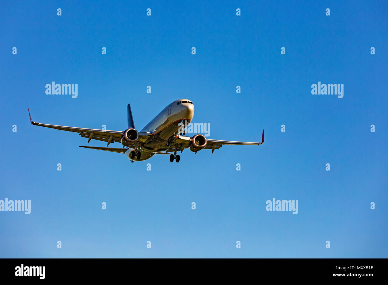 Large passenger plane flying in the blue sky Stock Photo