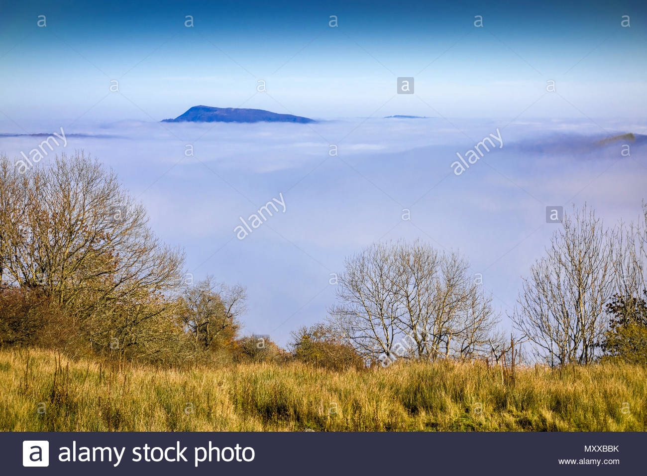 Fog caused by temperature inversion fill the River Usk valley. The peak of Great Skirrid (Big Skirrid) is in the distance; Monmouthshire, Wales, UK. Stock Photo