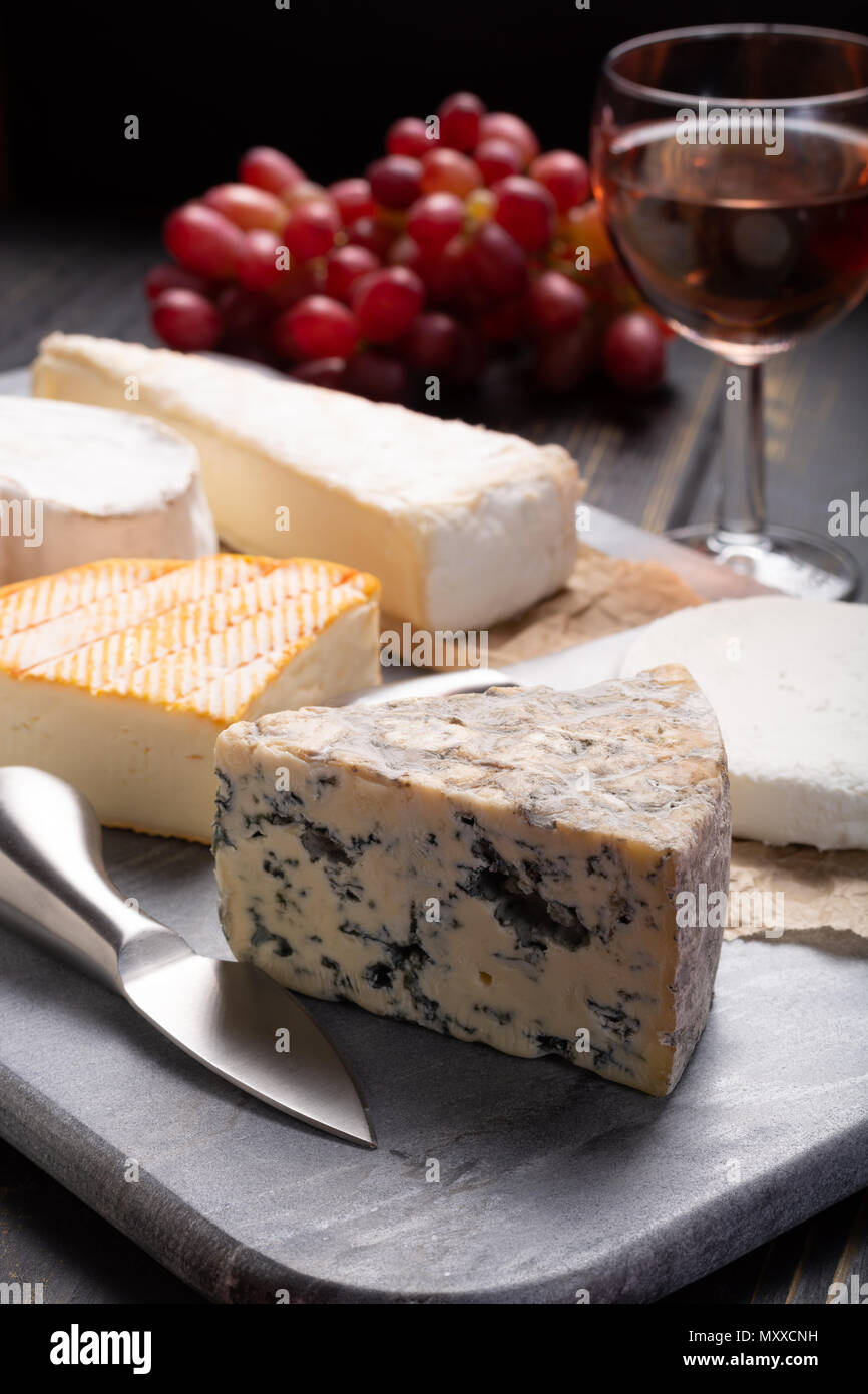French cheeses plate in assortment, blue cheese, brie, munster, soft goat cheese, Neufchatel - Stock Image