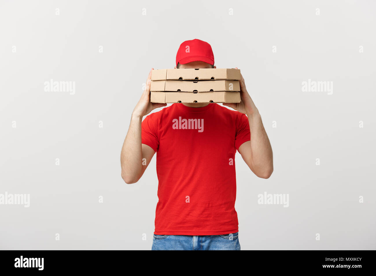 A Deliveryman hidden behind a large stack of pizza boxes he is carrying. Isolated over grey background. - Stock Image