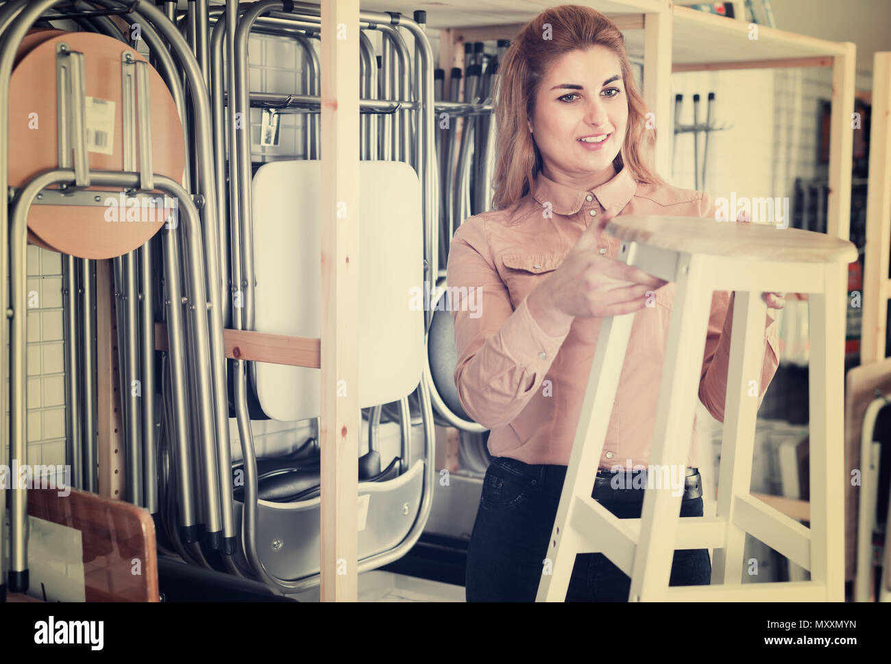 Young woman looking for new stylish tabouret for apartment in furniture salon - Stock Image