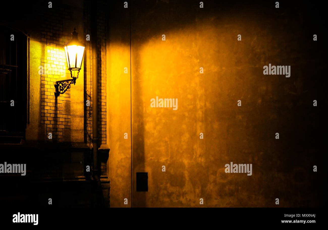 Old lantern illuminating a dark alleyway corner wall at night in Prague, Czech Republic. Photo almost monochromatic with brown yellow tones from the l - Stock Image