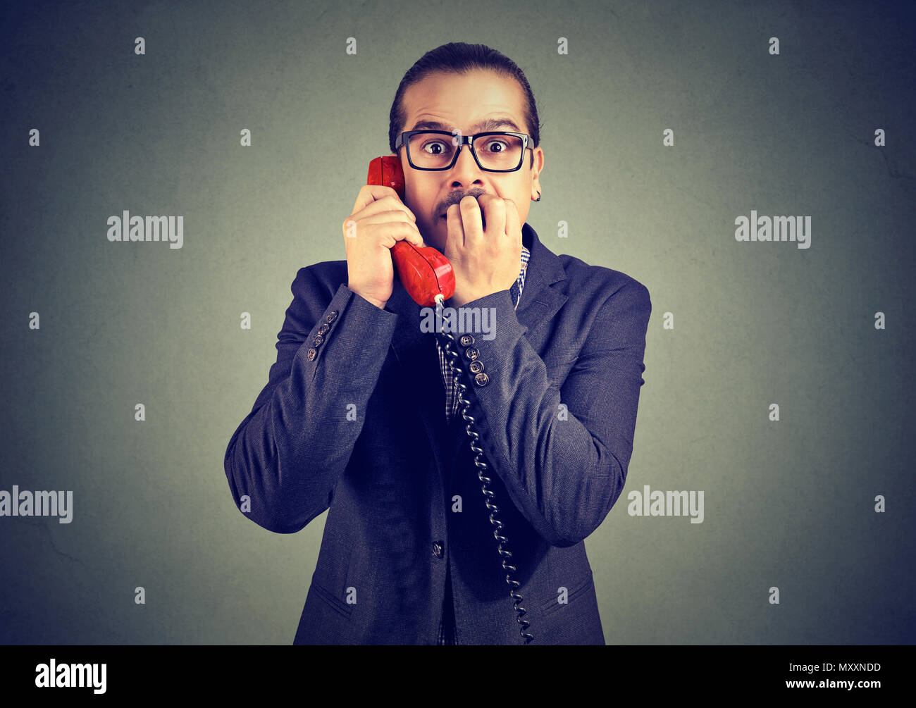 Stylish man in suit receiving shocking news on phone and looking at camera with fear. - Stock Image