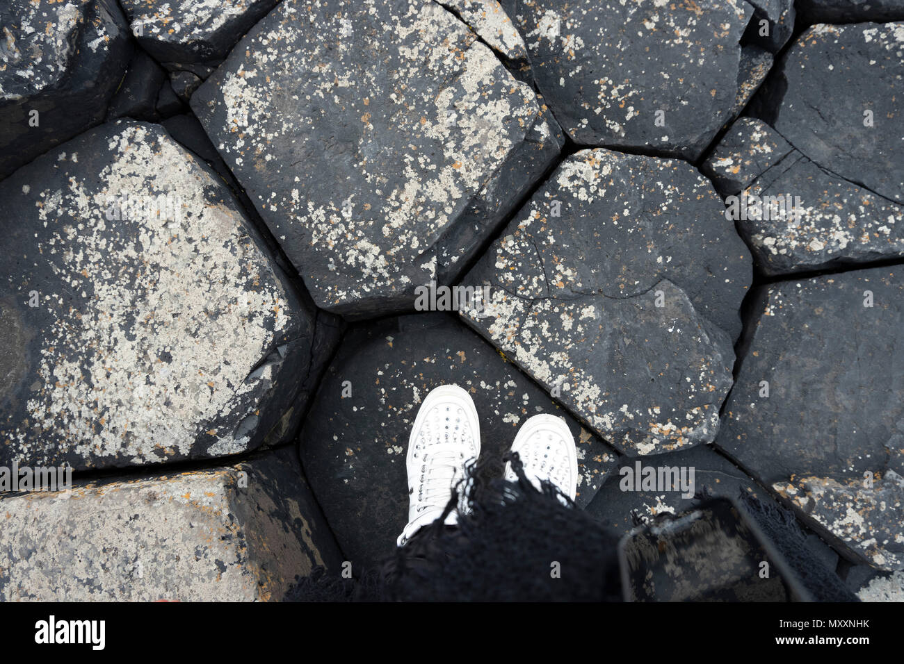 High angle view of legs in white shoes on black basalt stones, Giants Causeway, Northern Ireland - Stock Image