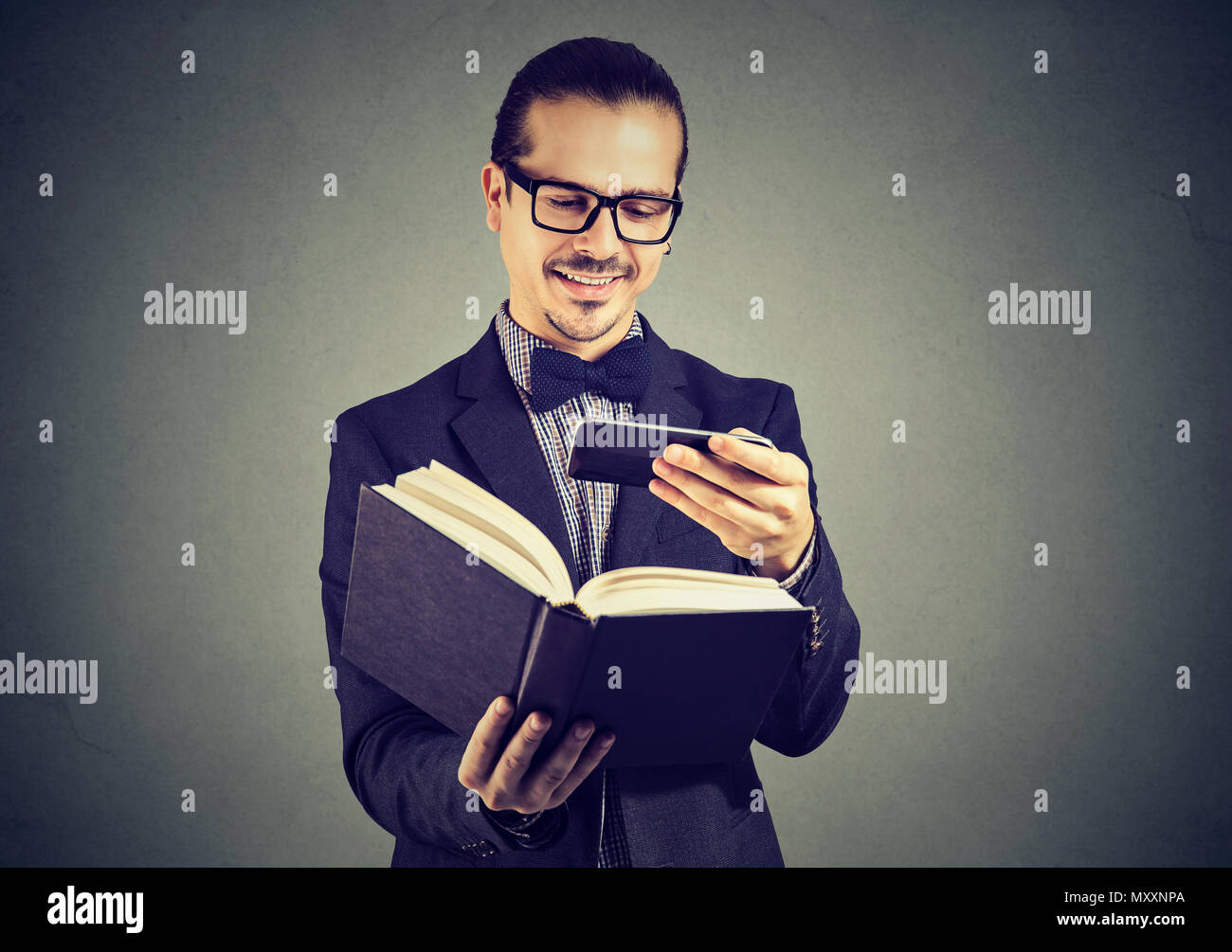 Young man in suit and glasses scanning information in book using phone and breaking copyrights. - Stock Image