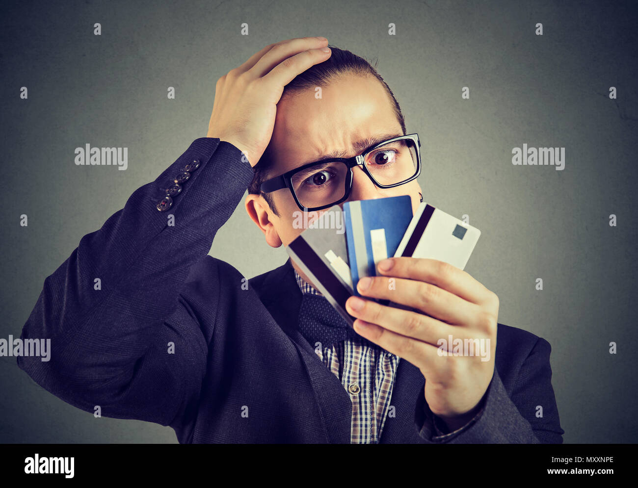 Young man in glasses holding credit cards and looking stressed with having money problems. - Stock Image