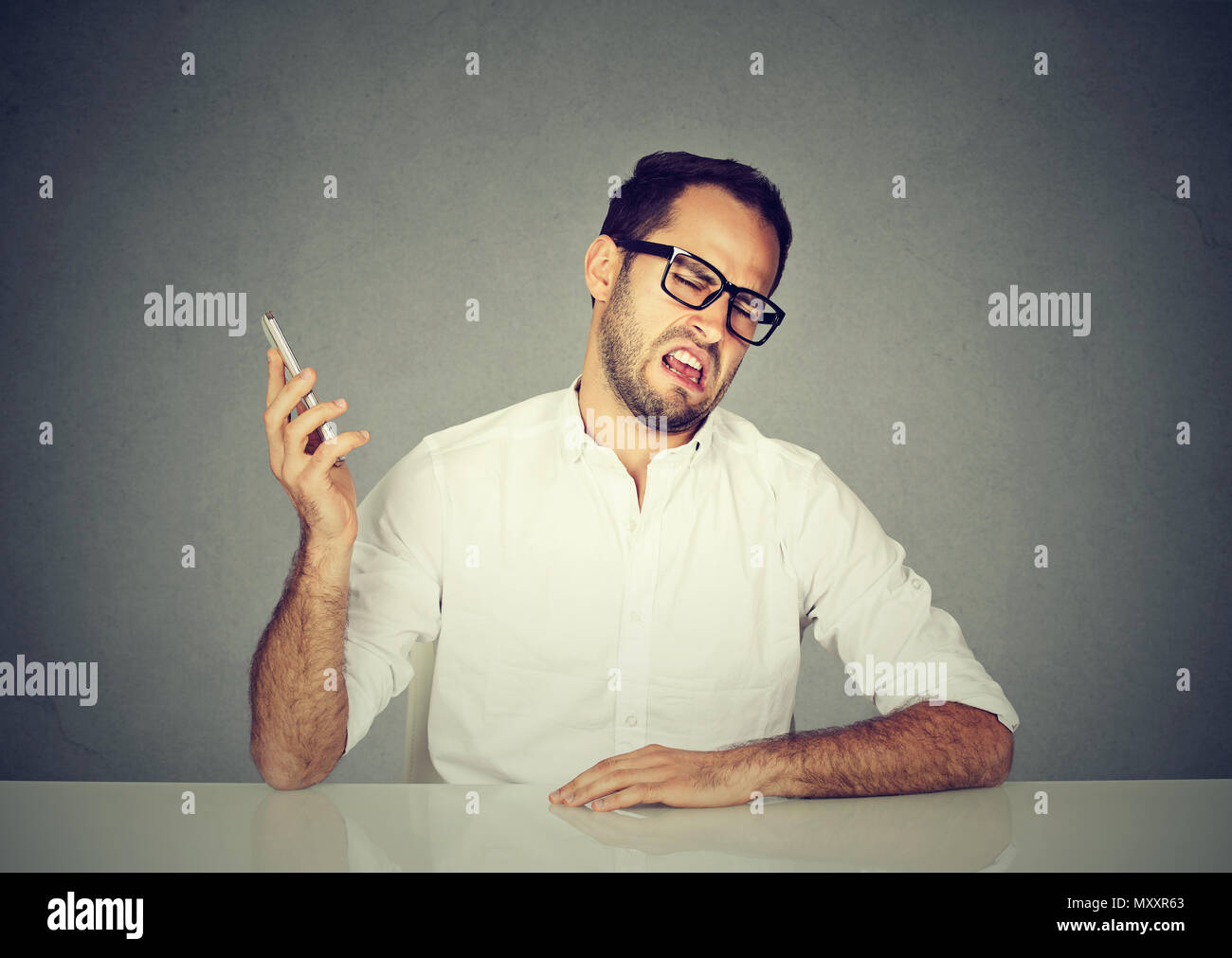 Man in white shirt and glasses grimacing and ignoring conversation partner while having phone call - Stock Image
