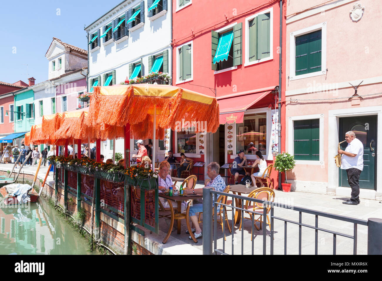 People dining to classical live music with a saxophone player  in Burano Island, Venice, Veneto, Italy alongside the canal under colourful orange umbr - Stock Image
