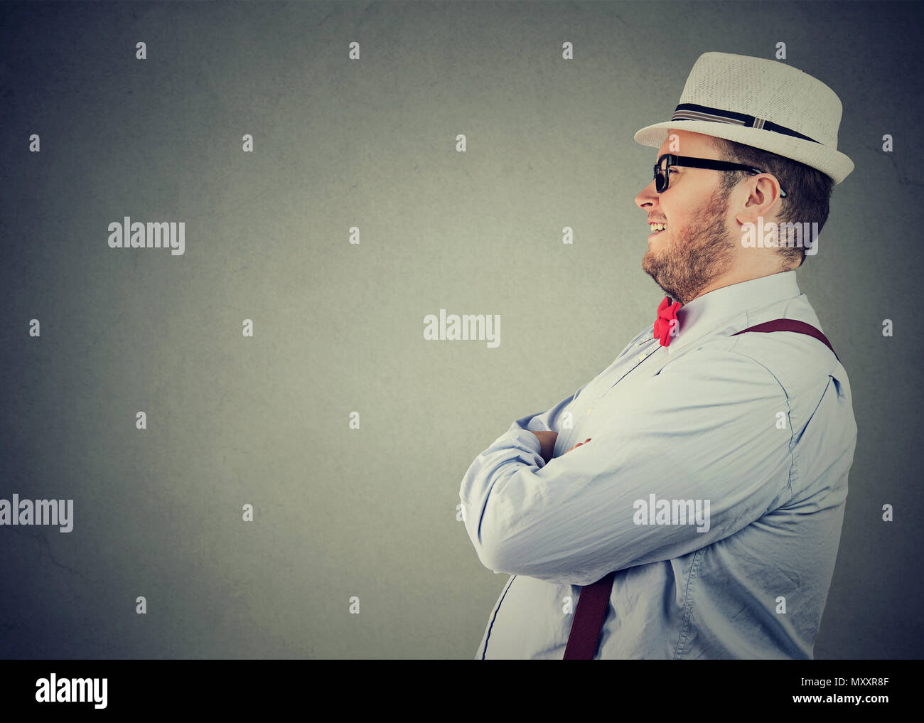 Side view of a chubby happy man in elegant outfit with bow tie and straw hat looking away confidently - Stock Image