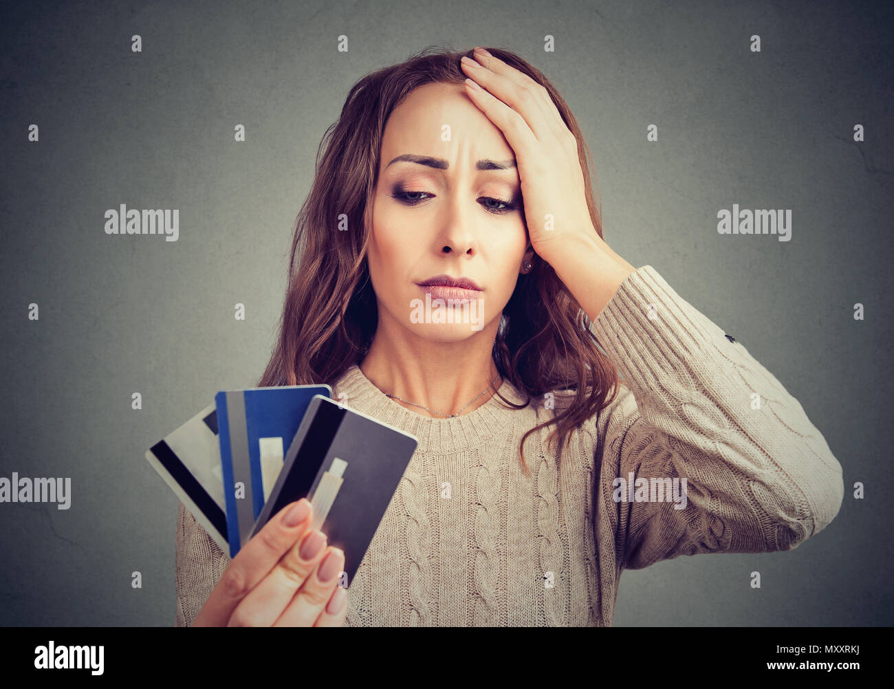 Young woman holding credit cards and looking stressed having financial problems. - Stock Image