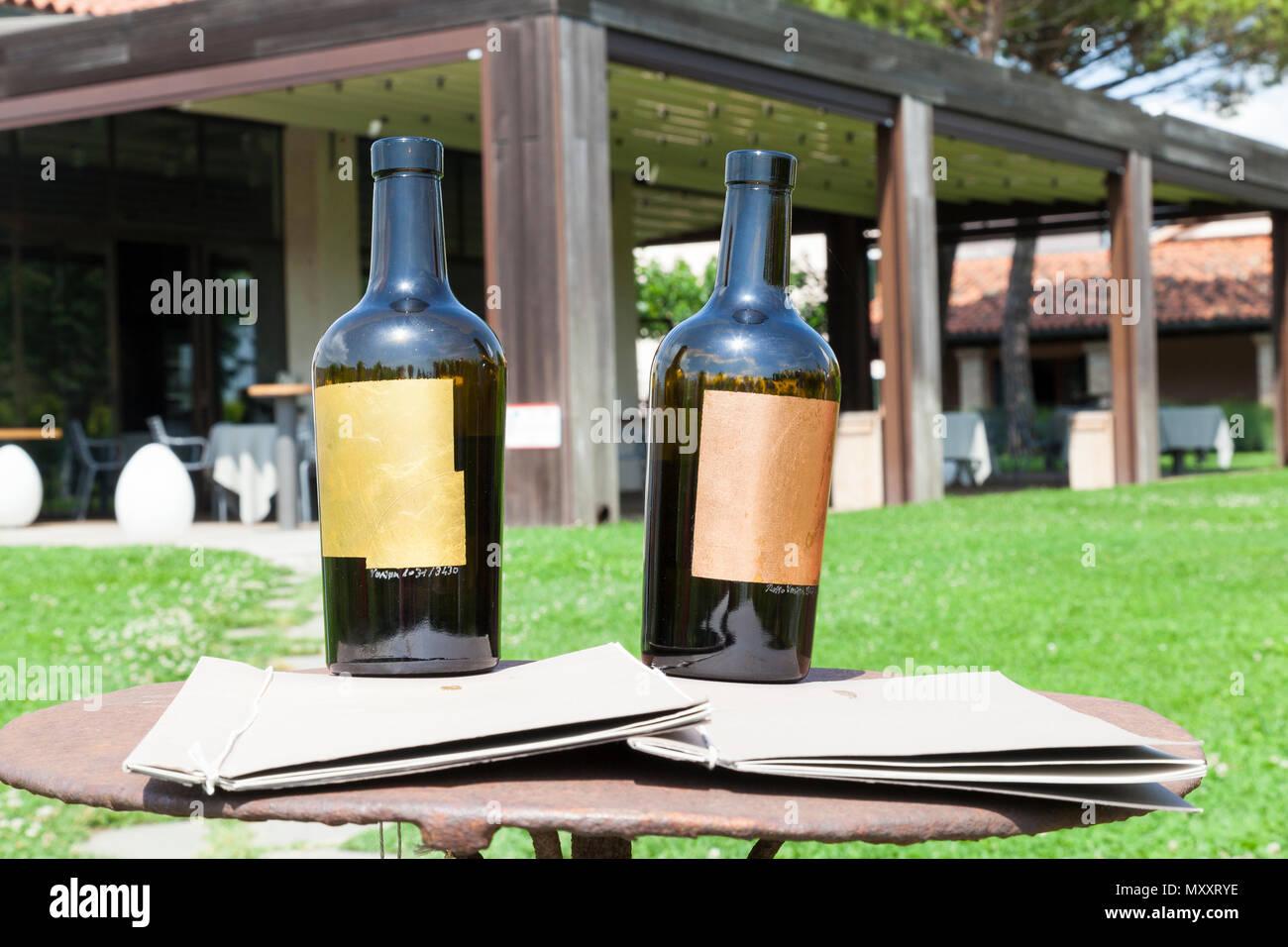 Venissa wine bottles at the winery, Mazzorbo Island, Venice, Veneto, Italy. Made from Murano glass with hand beaten Venetian gold leaf. Michelin star  - Stock Image