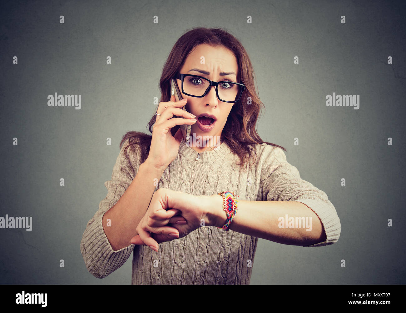 Young woman in glasses speaking on phone and gasping with fear being late to job - Stock Image