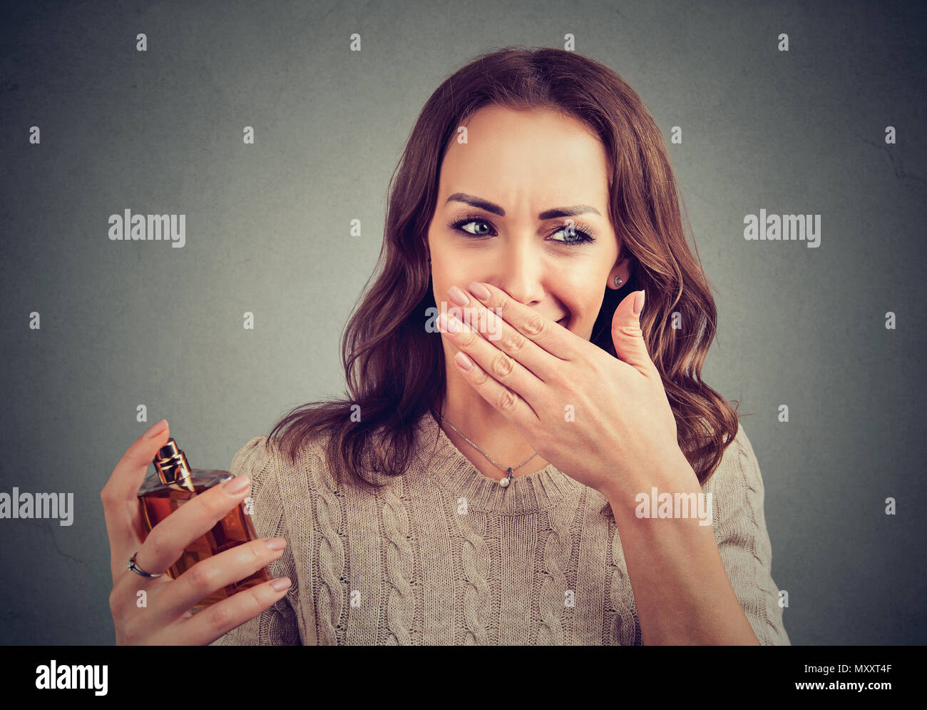Young woman disgusted with unpleasant stinky perfume holding nose. - Stock Image