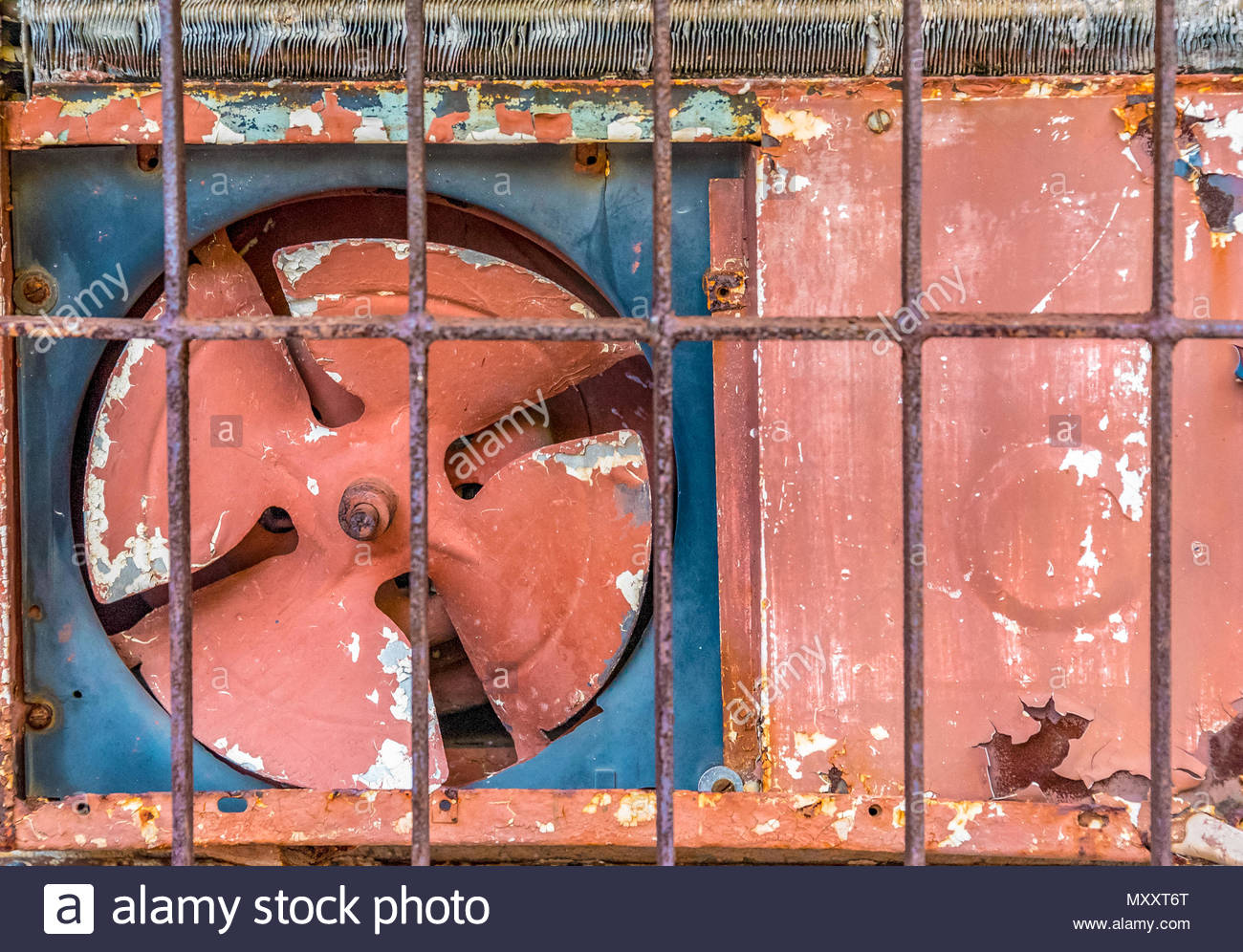 Oudoor side of an old rusty red air conditioner. Cubans manage to get the most incredible pieces of equipment in working condition - Stock Image