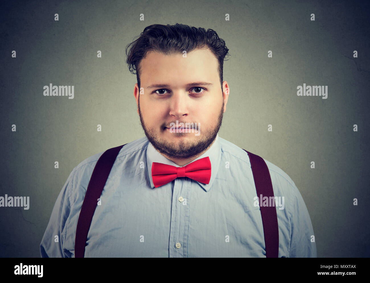 Young bearded chubby man wearing formal outfit with red bow tie looking contently at camera on gray - Stock Image