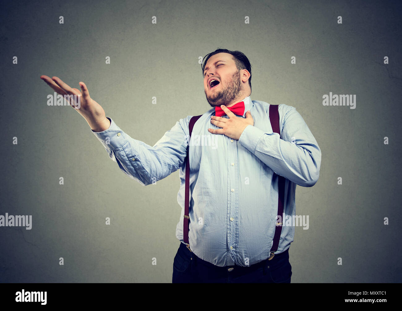 Young chubby man screaming in feelings of broken heart looking desperate while playing drama scene - Stock Image