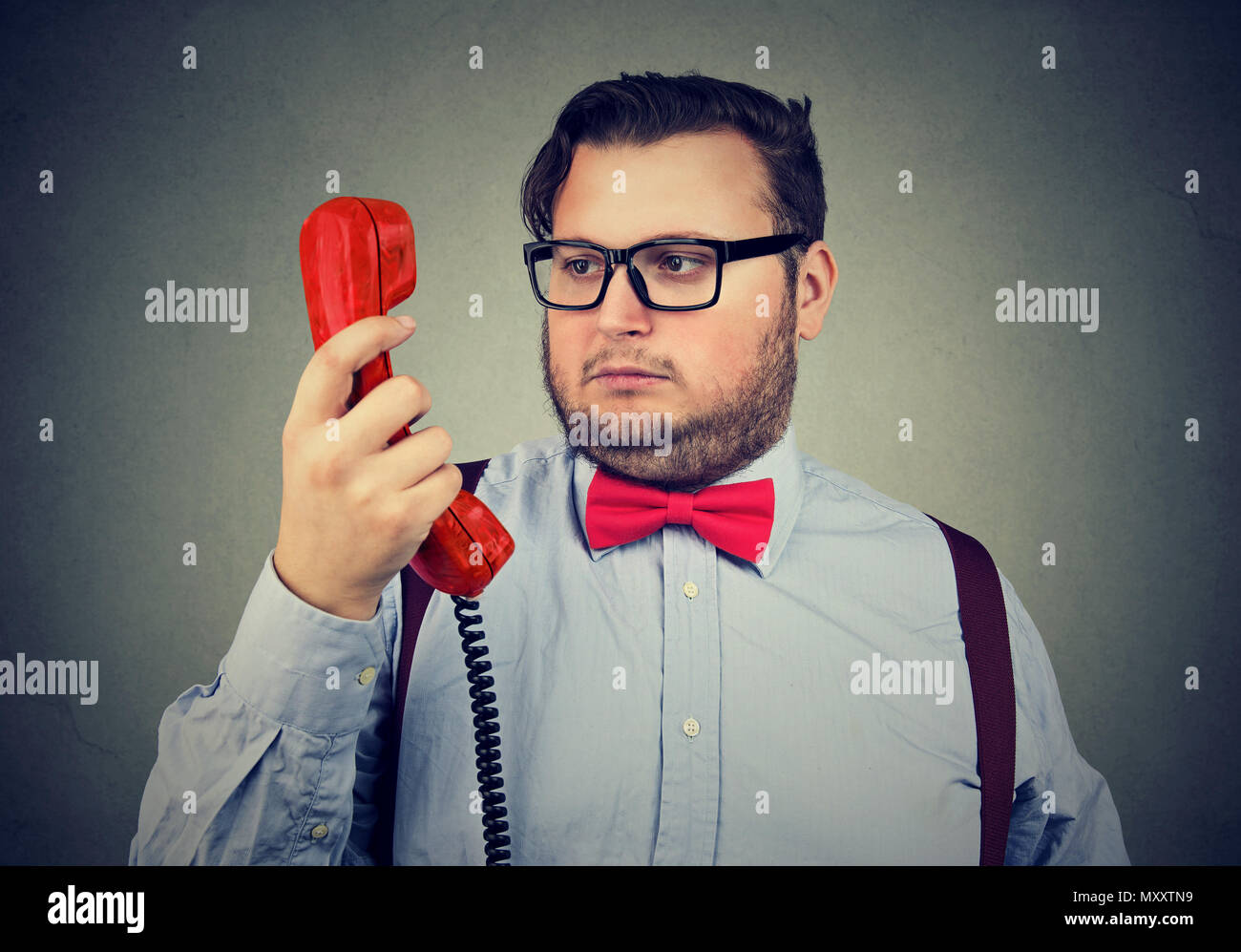 Formal chubby man in bow tie and glasses looking at handset in doubt and misunderstanding on gray - Stock Image