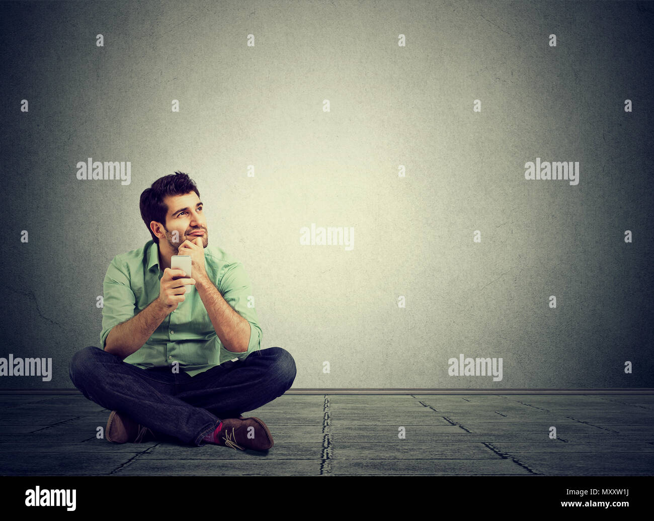 Handsome casual man sitting on floor with smartphone in hands and looking away in contemplation - Stock Image