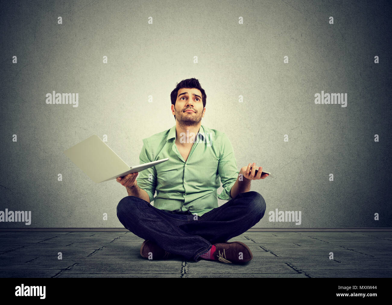 Casual man sitting on floor with laptop in hands while shrugging with shoulders in misunderstanding - Stock Image