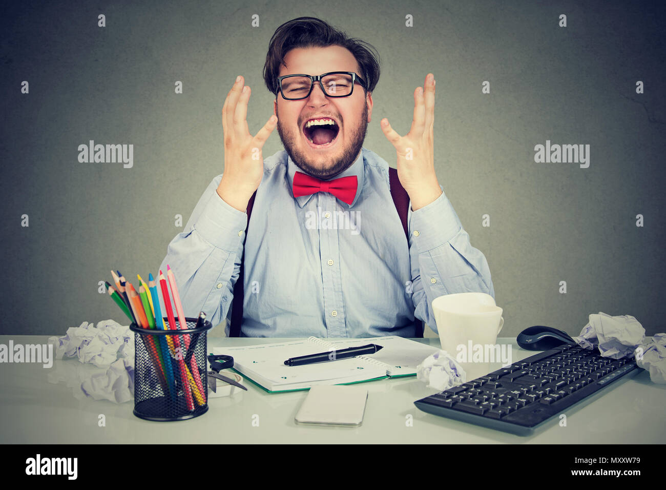 Stressed business man sitting at working place in chaos and yelling in frustration under pressure of time and workload - Stock Image
