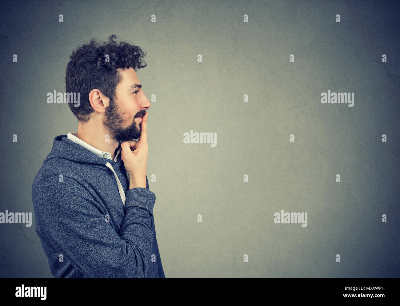 Side view of young hipster man touching lips and looking away in brainstorming while making decision. - Stock Image