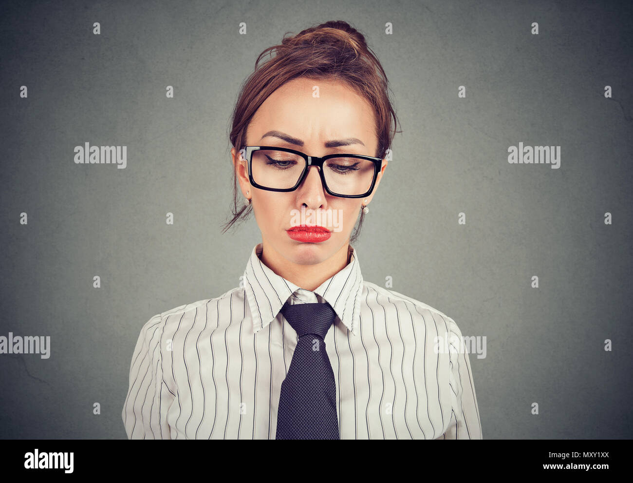 Beautiful woman in formal clothing and with red lips looking down in despair looking pity - Stock Image