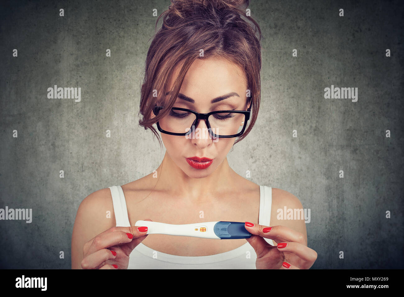Young woman shocked cannot believe her eyes while checking positive pregnancy test - Stock Image