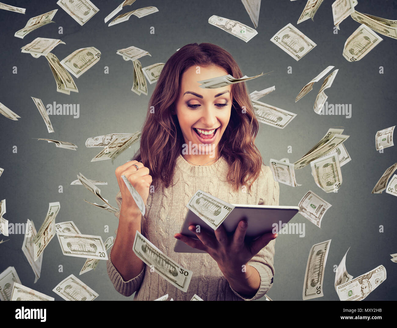 Cheerful woman with table happy with lottery win and holding fist up in money flying around - Stock Image