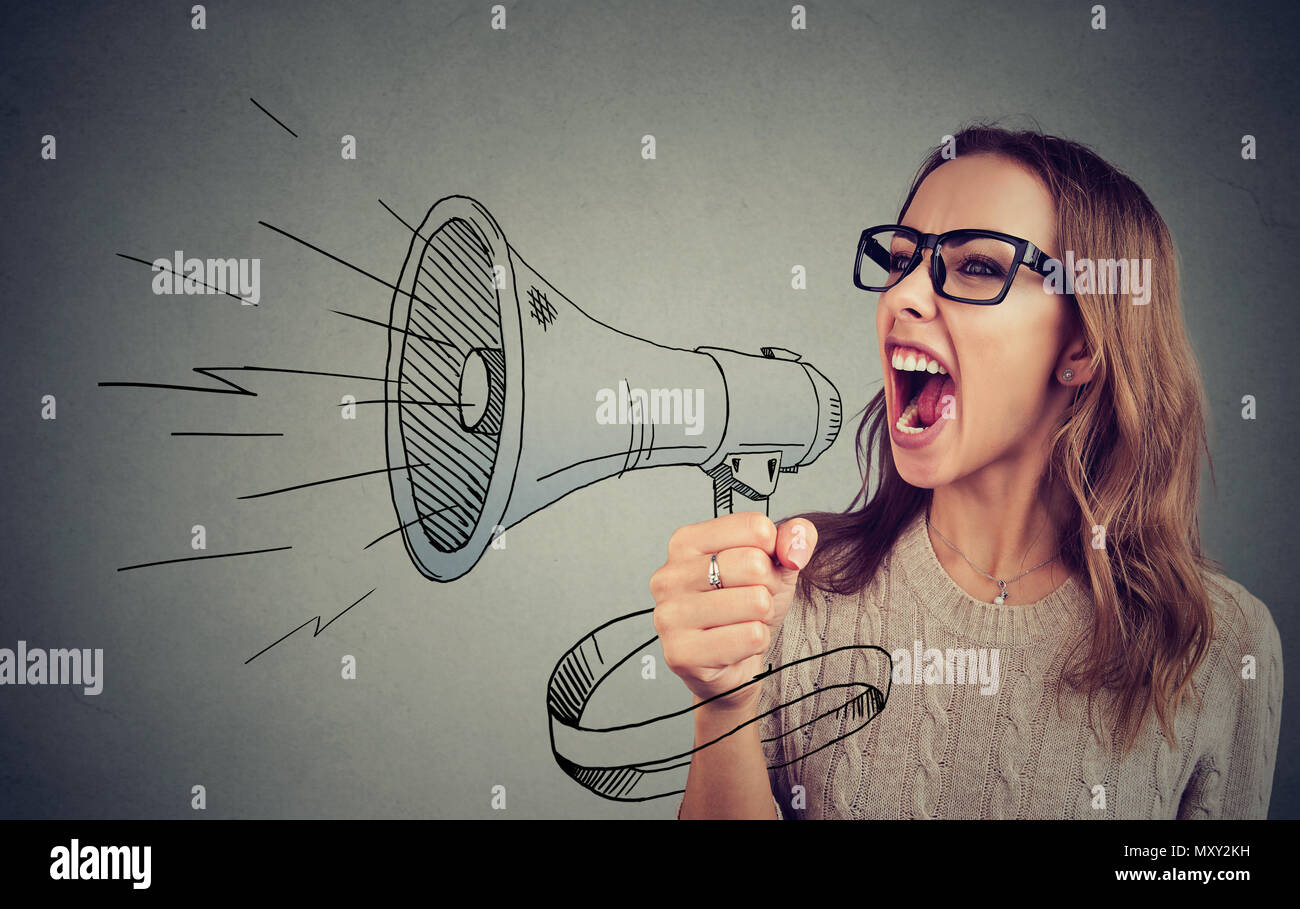 Expressive woman screaming loudly in megaphone spreading news and propaganda - Stock Image