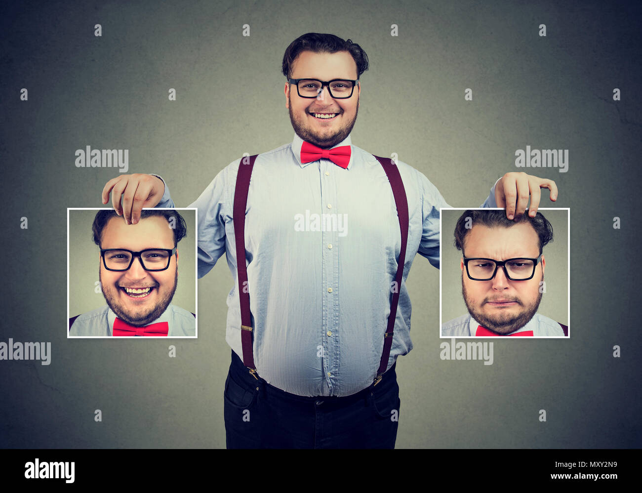 Young cheerful man in glasses holding pictures with good and bad emotions having mood swings and smiling at camera - Stock Image