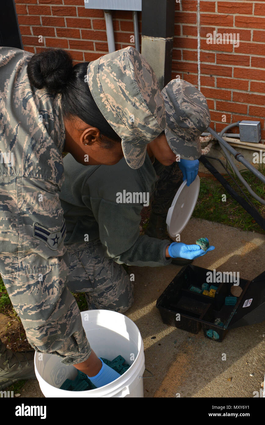 U.S. Air Force Airman 1st Class Francis Villamar and Airman 1st Class Anye Miller, 20th Civil Engineer Squadron entomology journeyman and apprentice, replace Contrac Blox in a bait box at Shaw Air Force Base, S.C., Dec. 16, 2016. The 20th CES entomology flight sets bait and maintains traps on base to remove pests such as mice, cats and insects. (U.S. Air Force photo by Airman 1st Class Destinee Sweeney) - Stock Image