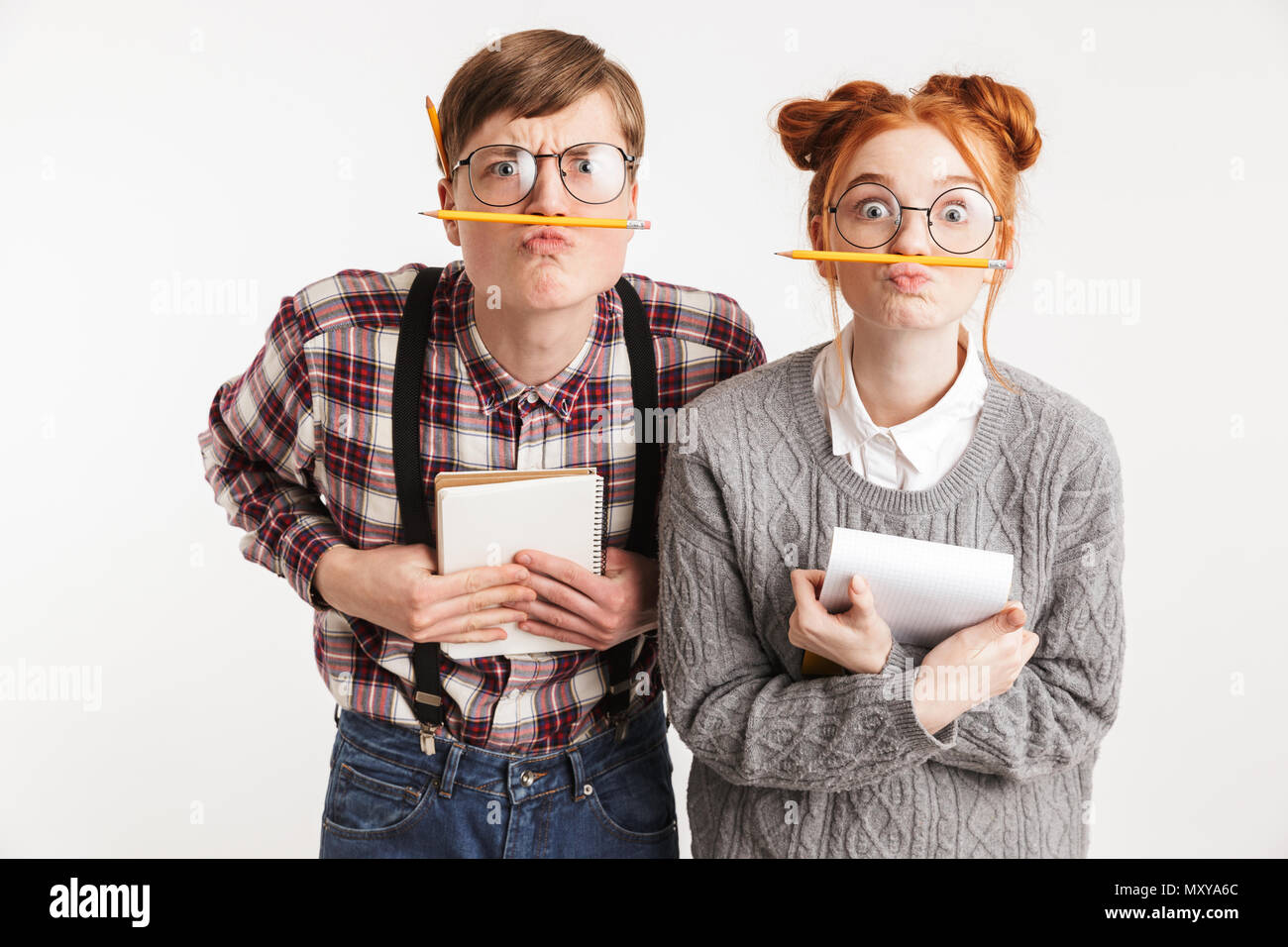Funny couple of school nerds grimacing while holding notepads and pencils isolated over white background - Stock Image