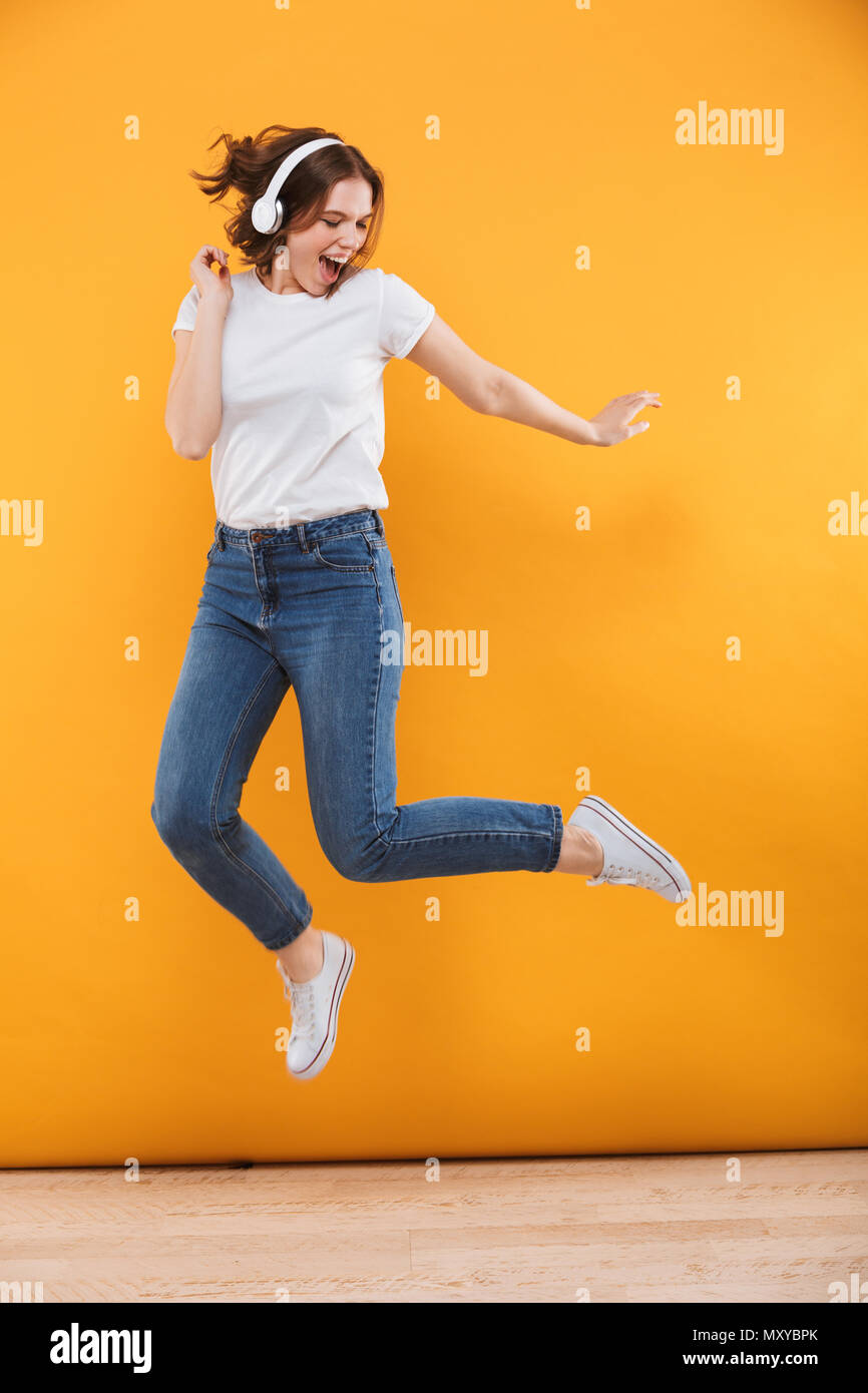 Image of emotional funny young woman jumping isolated over yellow