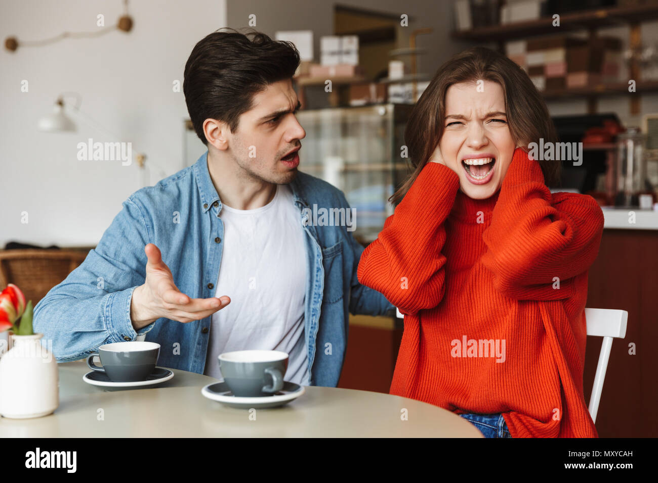 Disappointed couple woman and man 20s screaming and having quarrel while having coffee break in cafe - Stock Image