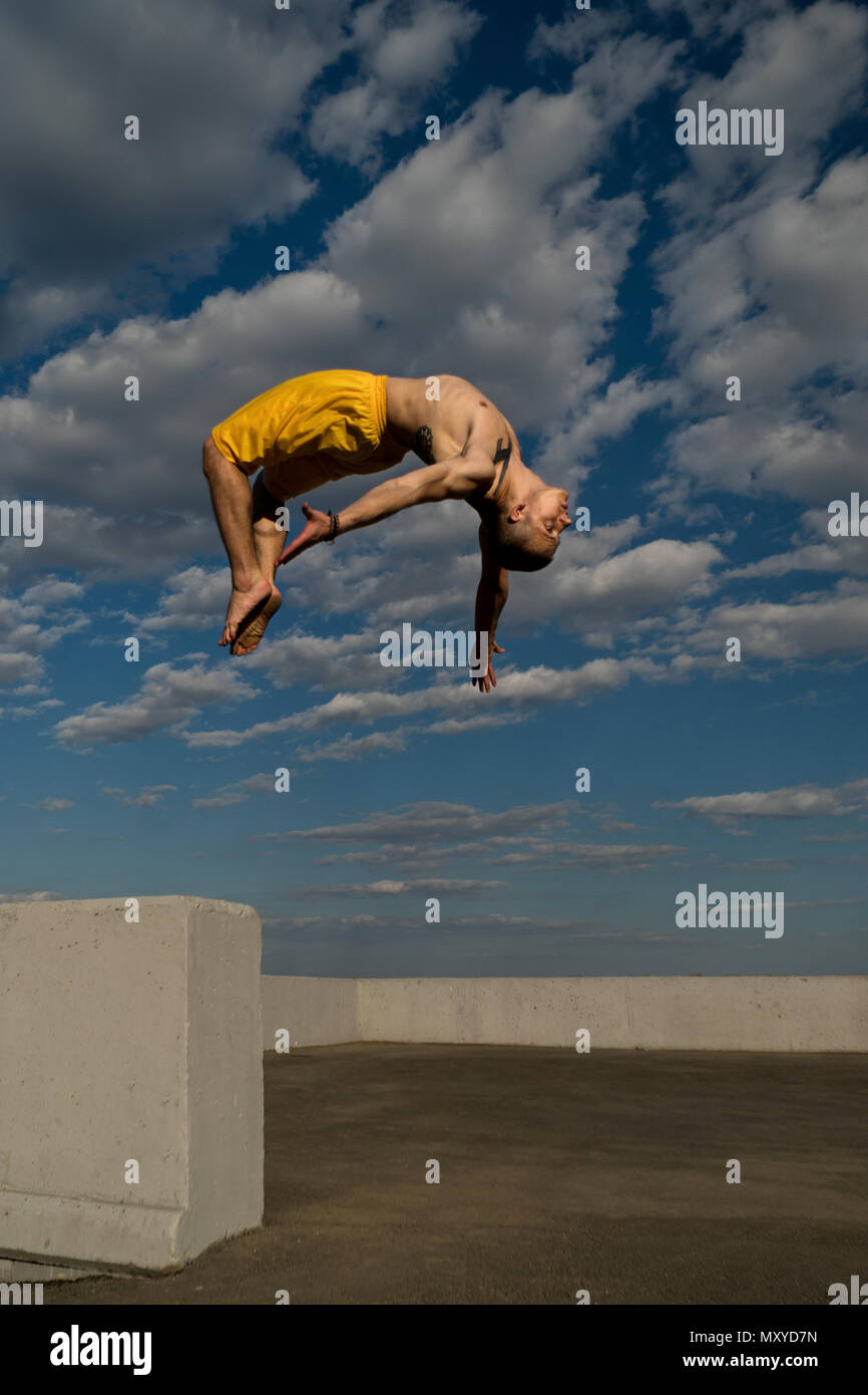 Tricking on street. Martial arts and elements of parkour. Man flips back barefoot. Shooted from bottom foreshortening against sky. - Stock Image
