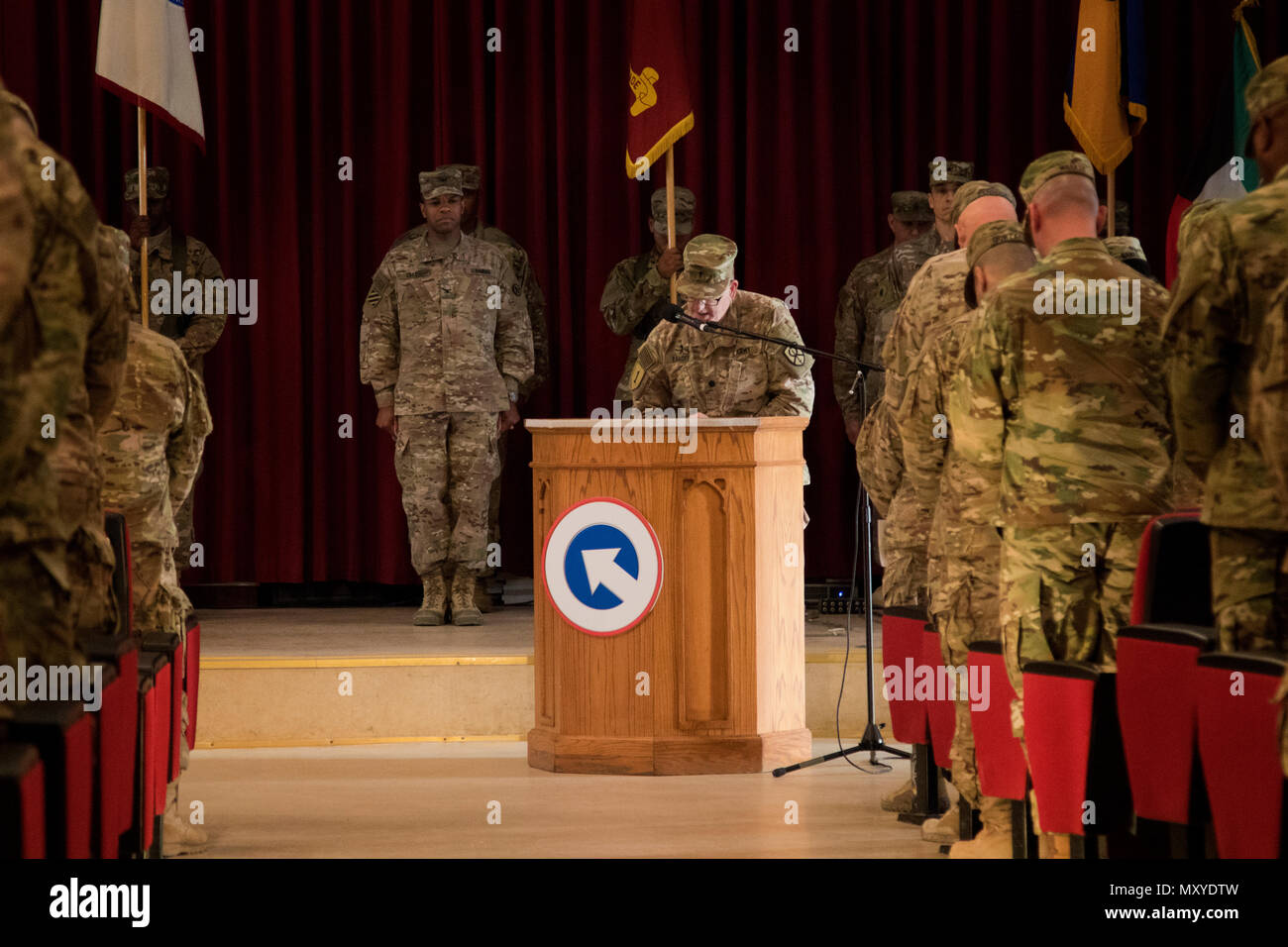 Lt. Col. David Langer, a chaplain with the 451st Sustainment Command (Expeditionary), reads the invocation before the 451st ESC and 316th ESC transfer of authority ceremony at Camp Arifjan, Kuwait, Dec. 23, 2016. (U.S. Army Photo by Staff Sgt. Dalton Smith) - Stock Image