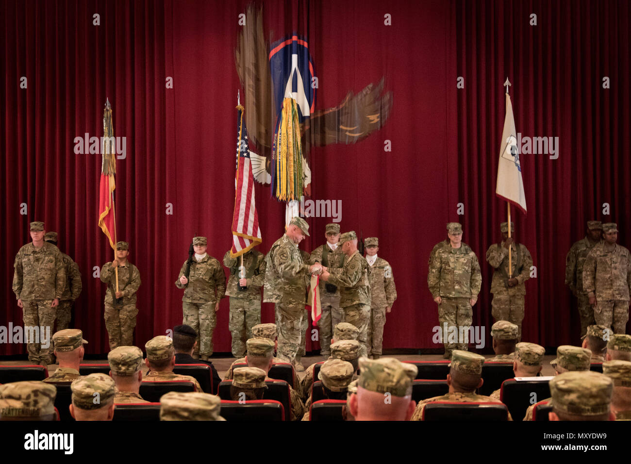Brig. Gen. Robert Harter, the commanding general of the 316th Sustainment Command (Expeditionary), and Command Sgt. Maj. Johnny McPeek, the senior enlisted advisor of the 316th ESC, uncase their colors during their transfer of authority ceremony from the 451st ESC at Camp Arifjan, Kuwait, Dec. 23, 2016. (U.S. Army Photo by Staff Sgt. Dalton Smith) - Stock Image
