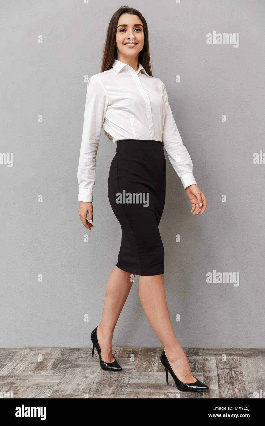 Full length portrait of adorable young woman 20s with long brown hair in white shirt and black skirt posing at camera with smile isolated over white b - Stock Image