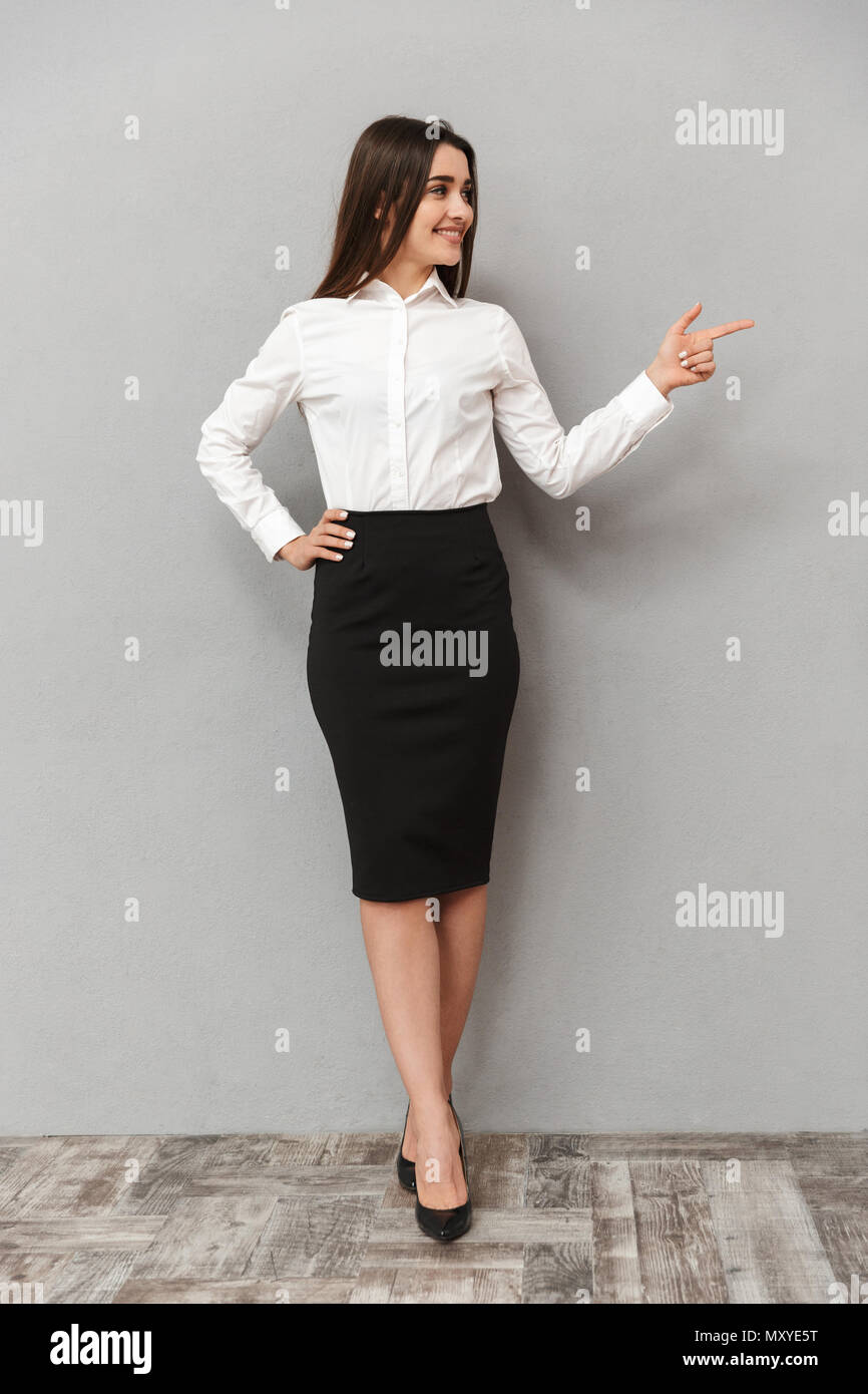 Full length portrait of brunette businesswoman 20s in white shirt and black skirt looking aside and pointing finger aside on copyspace isolated over g - Stock Image