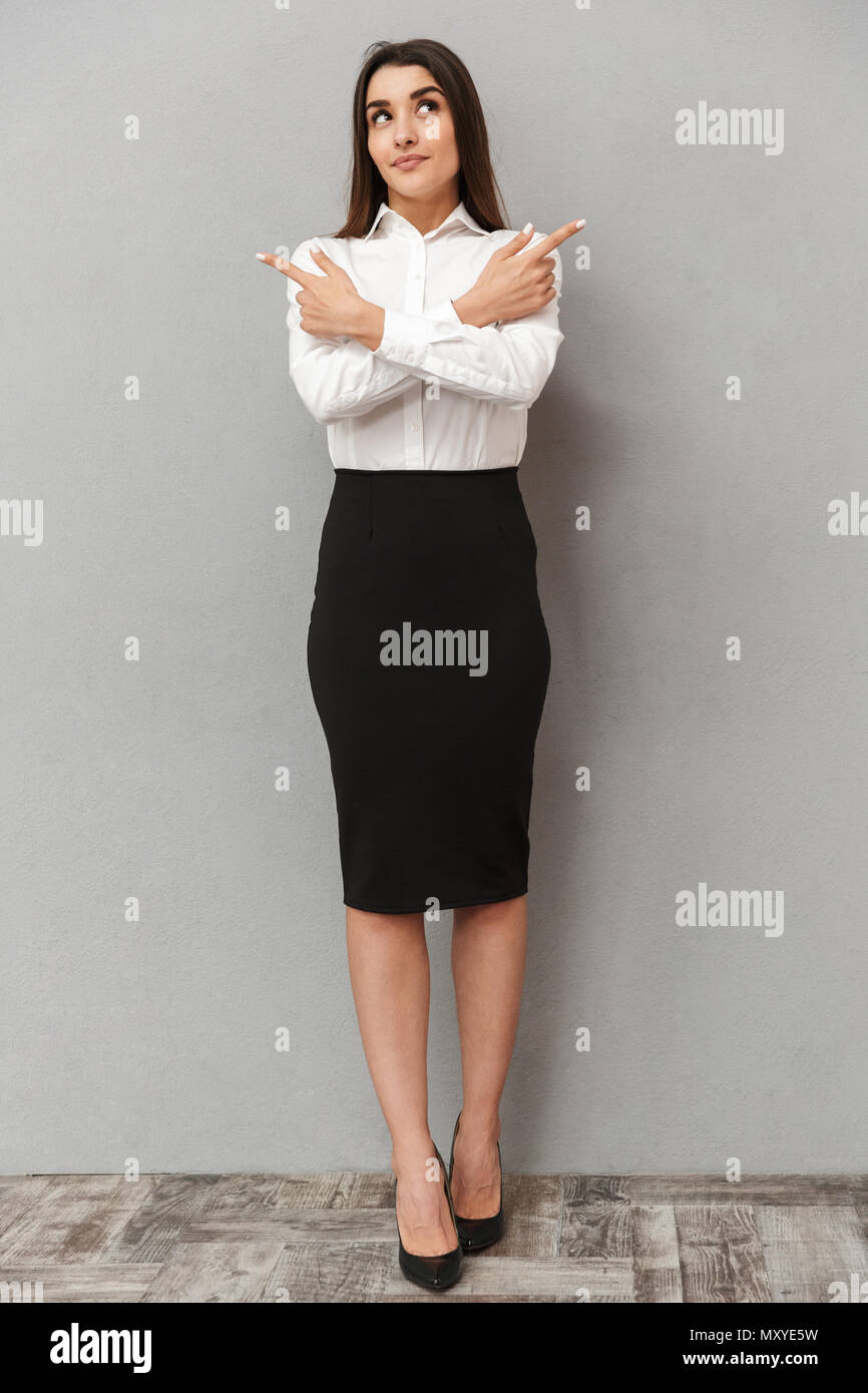 Full length portrait of brunette businesswoman 20s in white shirt and black skirt pointing fingers aside on copyspace with crossed arms isolated over  - Stock Image