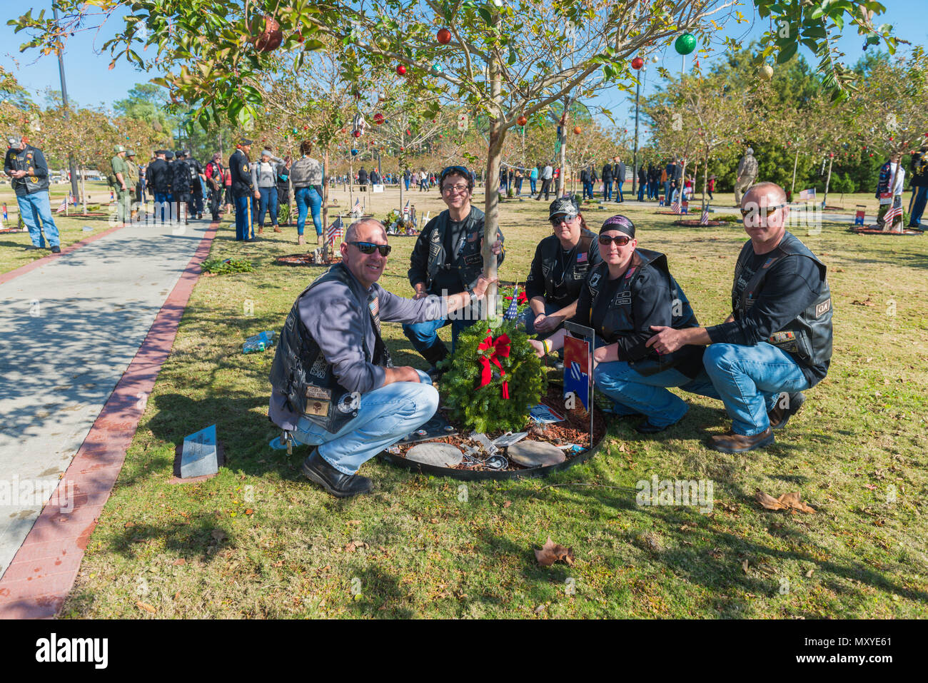 Members of the U.S. Military Vets motorcycle club of Surrency, Ga. honor Spc. Christian M. Neff at Tree # 373 following the Wreaths for Warriors Walk ceremony at Fort Stewart Dec. 17, 2016. U.S. Army Sgt. Maj. Jeff Logan (left) is from Spc. Neff's hometown in Ohio and is visiting the memorial in place of Neff's parents who could not be there. - Stock Image