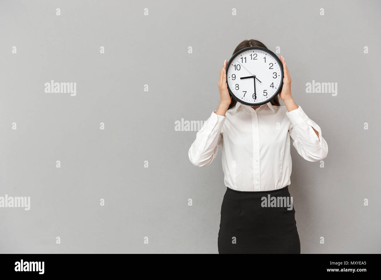 Photo of amusing businesswoman in formal wear covering face with big round clock isolated over gray background - Stock Image