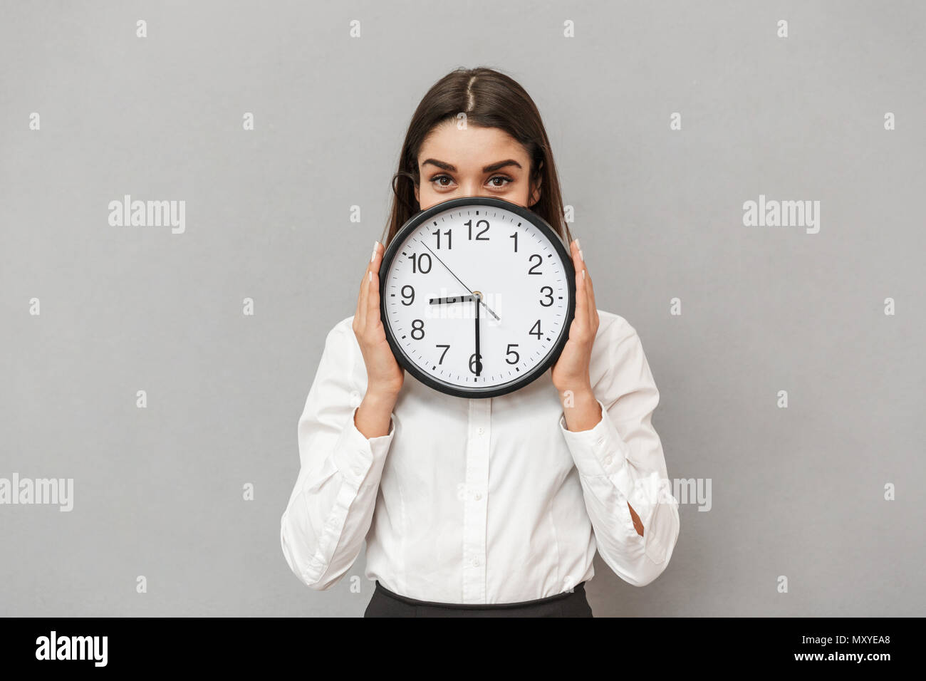 Photo of pretty business woman in formal wear covering face with big round clock isolated over gray background - Stock Image