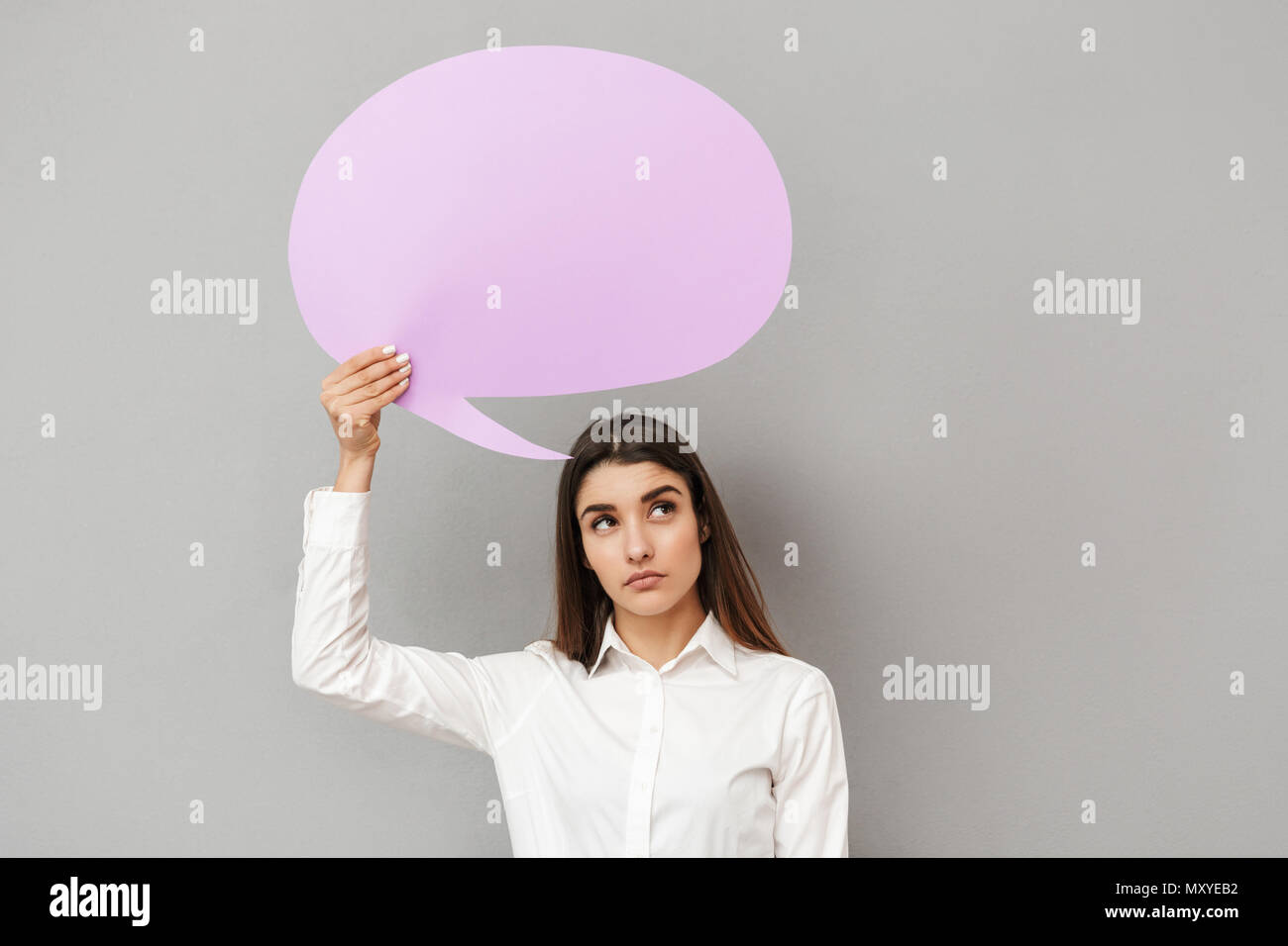 Photo of young woman in white shirt and black skirt with brooding look holding copyspace bubble for text isolated over gray background - Stock Image
