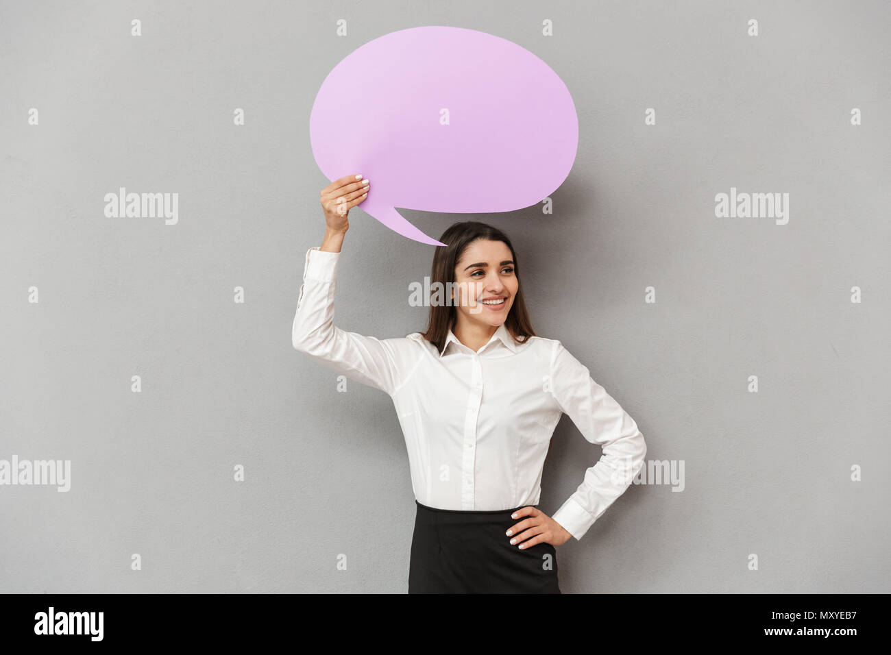 Photo of joyous woman in white shirt and black skirt looking aside with smile while holding copyspace bubble for text isolated over gray background - Stock Image