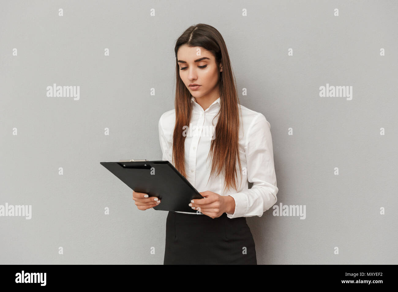 Photo of serious woman in white shirt and black skirt holding clipboard with documents in office isolated over gray background - Stock Image
