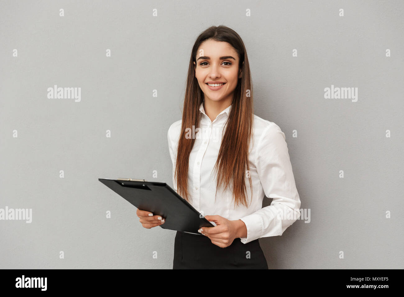 Photo of smiling woman in white shirt and black skirt holding clipboard with documents in office isolated over gray background - Stock Image