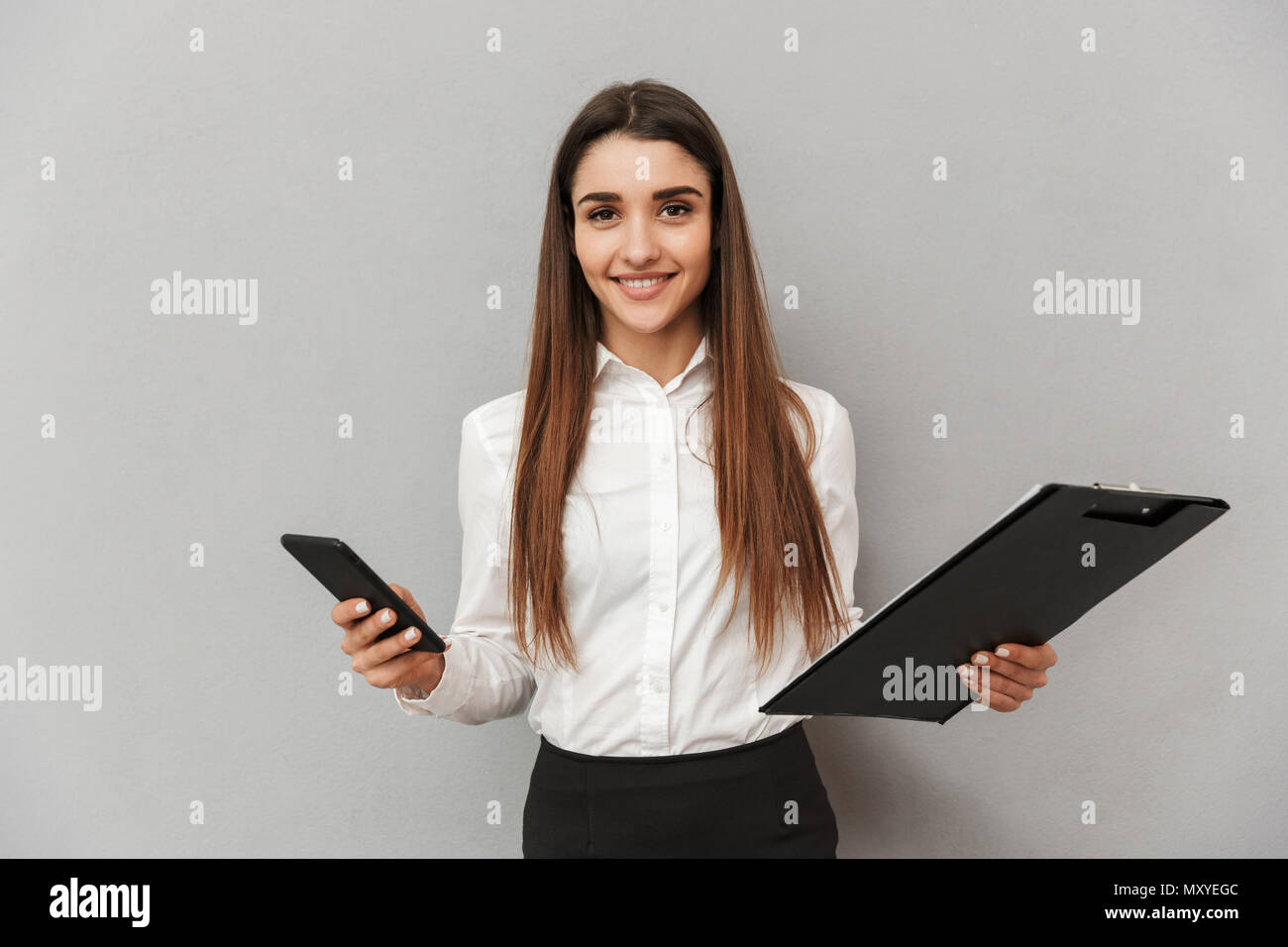 Photo of office woman 20s in white shirt and black skirt looking on camera with smile while holding documents and smartphone in both hands isolated ov - Stock Image