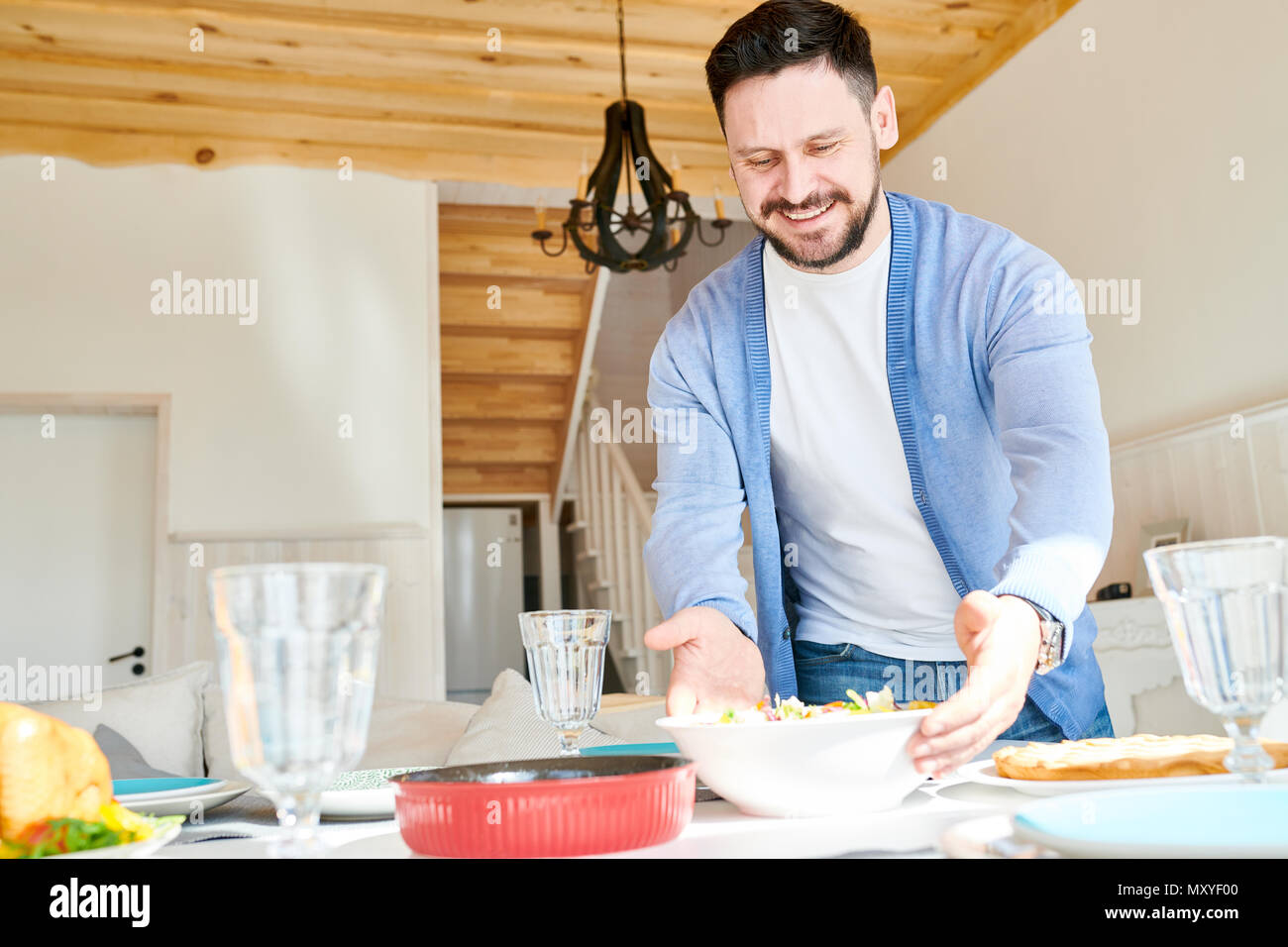 Portrait of mature bearded man setting table and smiling happily while waiting for guests at dinner in sunlit dining room at home, copy space - Stock Image